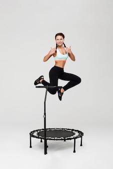 Het jonge atleet springen die stelt stelt en duimen toont