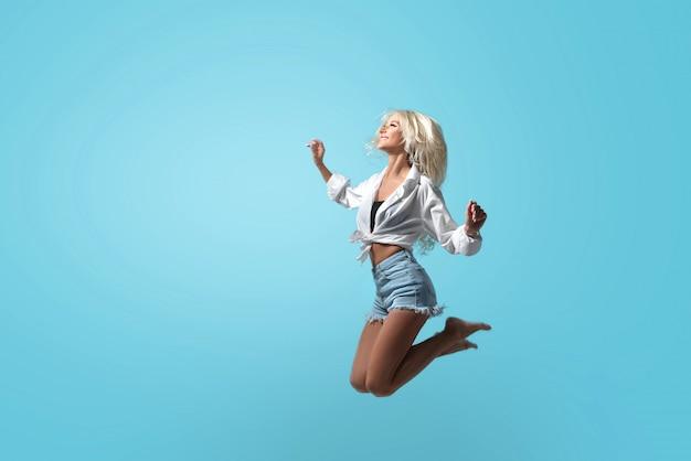 Het jonge atletische blonde meisje in de zomer kleedt hoogspringen op een geïsoleerde blauwe ruimte in studio