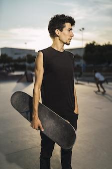 Het jonge atletische mannetje met een zwarte uitrusting die een skateboard met van hem houdt dient de zak in