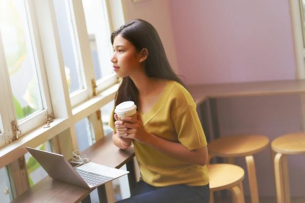 Het jonge aziatische document van de meisjesholding vormt en drinkt hete koffie, gebruikslaptop computer en ontspanning Premium Foto