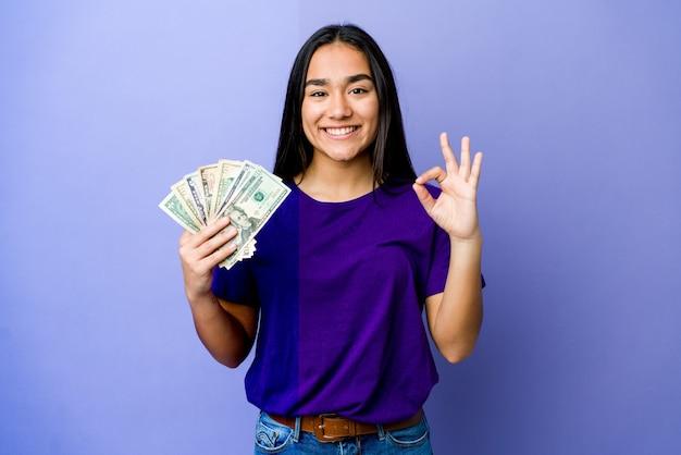 Het jonge aziatische geld van de vrouwenholding dat op purpere muur wordt geïsoleerd vrolijk en zeker tonend ok gebaar.