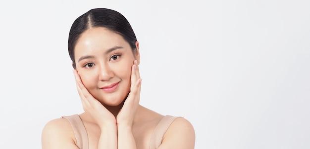 Het jonge aziatische gezicht van de vrouwenschoonheid maakt huidverzorgingsschoonheidsmiddel goed en toont natuurlijke wellness zachte en stevige en tijdloze gezichtshuid. zij ziet er jonger of jeugdig uit. studio opname witte muur.