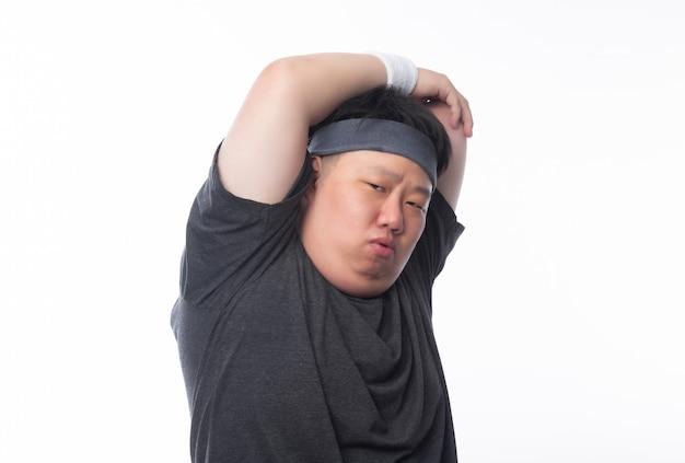 Het jonge aziatische grappige vette sportmens uitrekken zich vóór geïsoleerde oefening