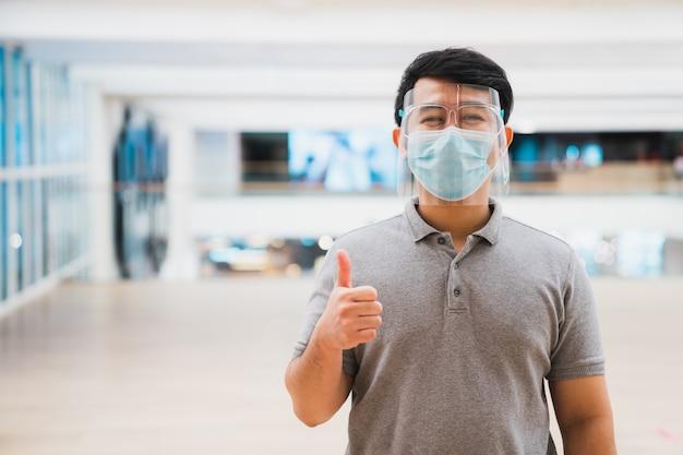 Het jonge aziatische het gezichtsschild en masker die van de mensenslijtage in winkelcomplex glimlachen