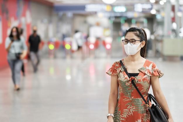 Het jonge aziatische meisje dat chirurgisch gezichtsmasker draagt beschermt coronavirusverbuiging
