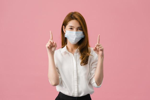 Het jonge aziatische meisje dat medisch gezichtsmasker draagt toont iets op lege ruimte met gekleed in een casual doek en kijkt naar camera geïsoleerd op roze achtergrond.