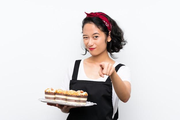 Het jonge aziatische meisje die veel muffincake houden over geïsoleerde witte muur richt vinger op u met een zekere uitdrukking