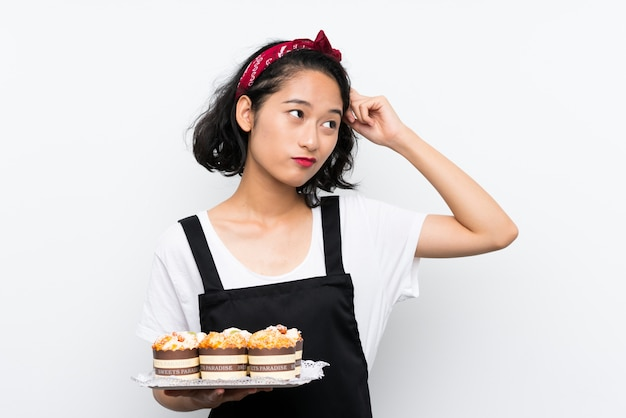 Het jonge aziatische meisje die veel muffincake houden twijfels hebben en met verwarren gezichtsuitdrukking