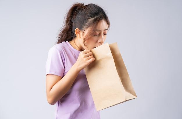 Het jonge aziatische meisje kokhalst in een papieren zak