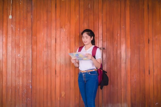 Het jonge aziatische meisje leest de kaart