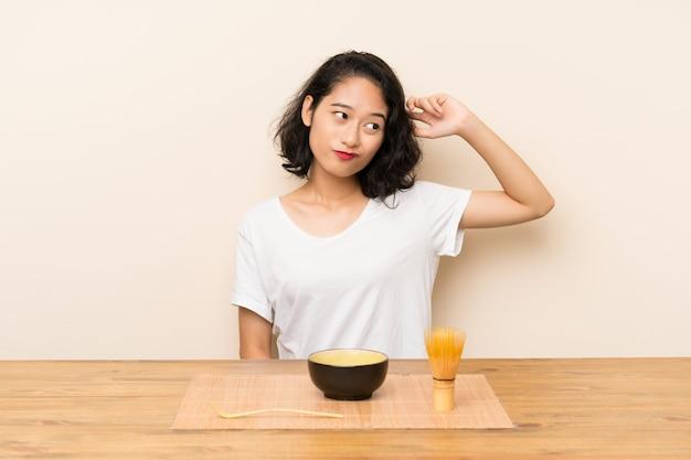 Het jonge aziatische meisje met theematcha die twijfels hebben en verwart gezichtsuitdrukking
