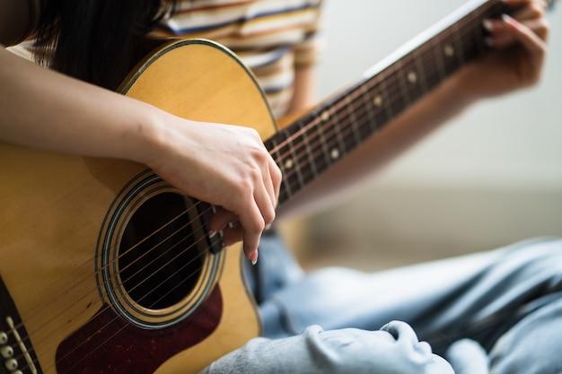 Het jonge aziatische meisje oefent thuis gitaar en componeert muziek