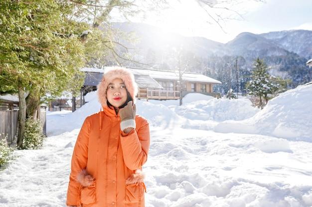 Het jonge aziatische meisje op sneeuw in shirakawa-gaat, japan.