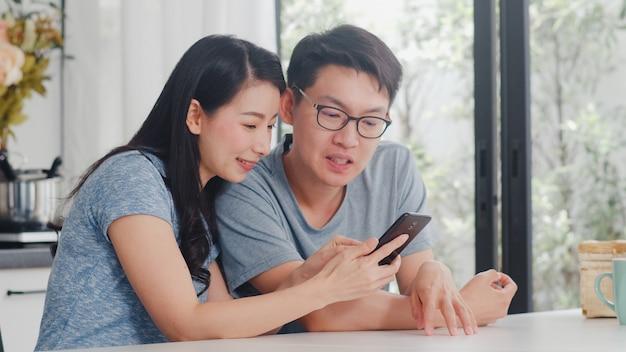 Het jonge aziatische paar geniet van thuis online winkelend op mobiele telefoon. lifestyle jonge man en vrouw gelukkig kopen e-commerce na het ontbijt in de moderne keuken in huis in de ochtend.