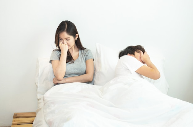 Het jonge aziatische paar in bed die problemen hebben en crisisman en vrouwenhanden behandelen hoofd met verward