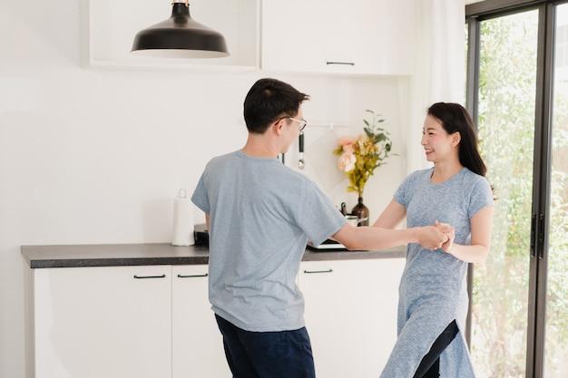 Het jonge aziatische paar luistert naar muziek en het dansen na het hebben van ontbijt thuis. de aantrekkelijke japanse vrouw en de knappe man genieten van samen doorbrengend tijd in moderne keuken bij huis in de ochtend.