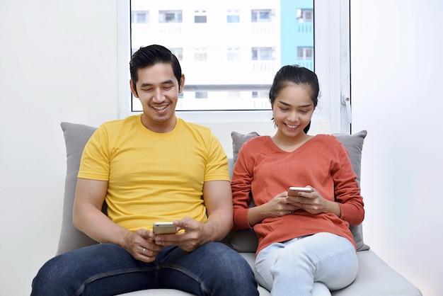 Het jonge aziatische paar ontspannen samen met het gebruiken van mobiele telefoon
