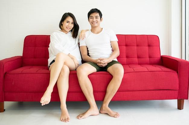Het jonge aziatische paar ontspannen samen op het rode bankbed in de woonkamer.