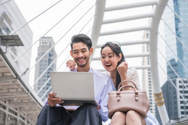 Het jonge aziatische paar zit met behulp van laptop met opgewonden en vrolijk