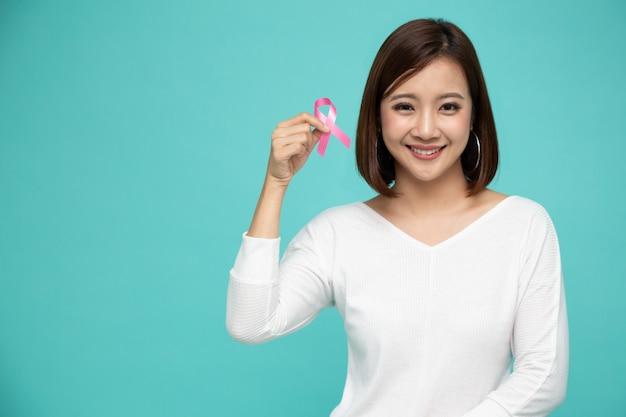 Het jonge aziatische roze lint van borstkanker van de vrouwenholding over geïsoleerde lichtgroene muur