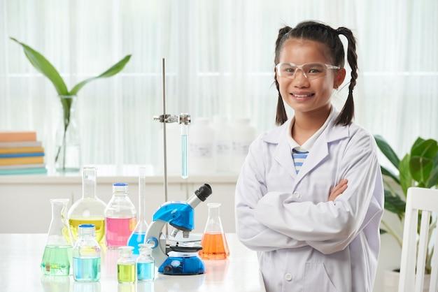 Het jonge aziatische schoolmeisje stellen in chemieklasse met kleurrijke flesjes