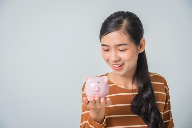Het jonge aziatische spaarvarken van de vrouwenholding
