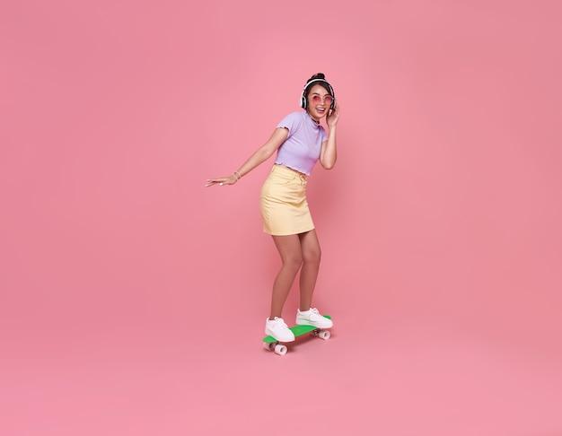 Het jonge aziatische tienermeisje spelen op skateboard met het dragen van draadloze hoofdtelefoons die aan muziek op roze muur luisteren.