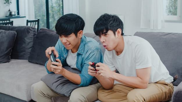 Het jonge aziatische vrolijke paar speelt thuis spelen, tien koreaanse lgbtq-mannen die joystick gebruiken die grappig gelukkig ogenblik samen op bank in woonkamer hebben bij huis.
