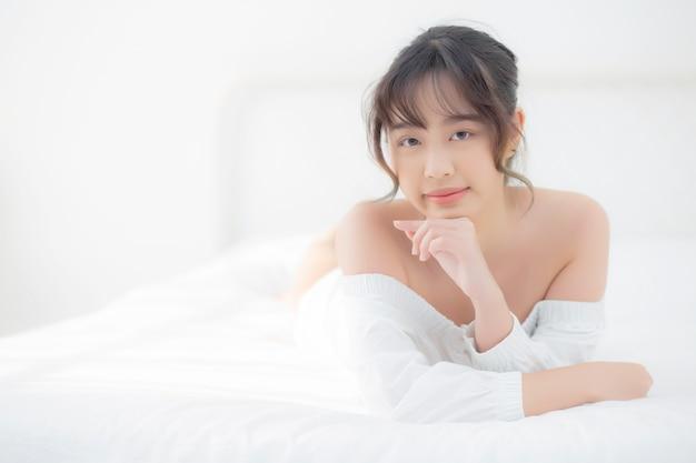 Het jonge aziatische vrouw liggen en glimlachen terwijl ontwaken
