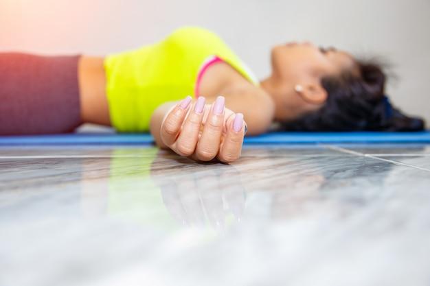 Het jonge aziatische vrouw praktizeren in een yogastudio