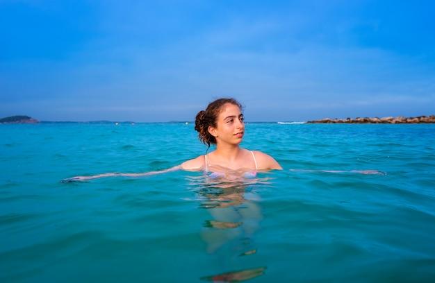 Het jonge bad van het vrouwenmeisje in het ibiza-strand