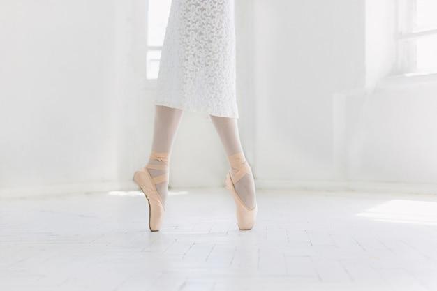 Het jonge ballerina dansen, close-up op benen en schoenen, die zich in pointes bevinden