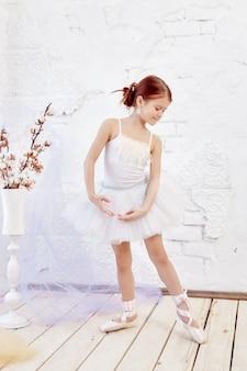 Het jonge ballerinameisje treft voorbereidingen voor een balletvoorstelling. weinig prima ballet. meisje in een witte baljurk en pointe bij het raam