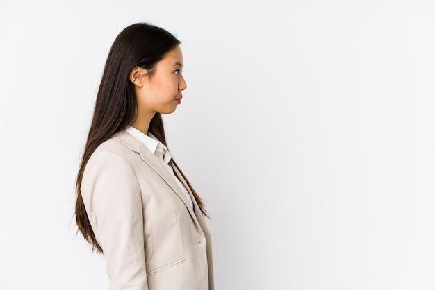 Het jonge bedrijfs chinese vrouw geïsoleerde links staren, stelt zijdelings.