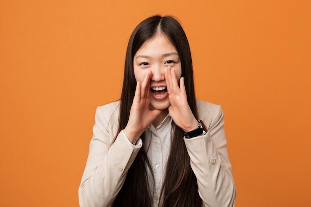 Het jonge bedrijfs chinese vrouw schreeuwen opgewekt aan voorzijde.