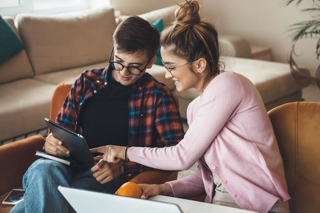 Het jonge bedrijfspaar werkt vanuit huis in een tablet en laptop die in leunstoel glimlachen