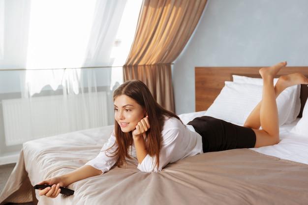 Het jonge bedrijfsvrouw ontspannen in hotelruimte en het kijken tv
