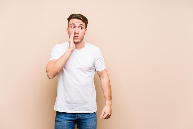 Het jonge blanke man geïsoleerd stellen zegt een geheim heet remmend nieuws en kijkt opzij