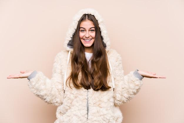 Het jonge blanke vrouw geïsoleerd poseren maakt schaal met armen, voelt zich gelukkig en zelfverzekerd.