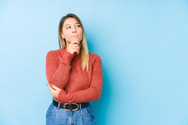 Het jonge blanke vrouw stellen geïsoleerd zijwaarts met twijfelachtige en sceptische uitdrukking op zoek.
