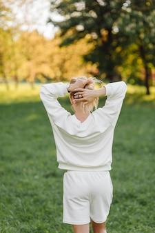 Het jonge blonde meisje draagt een witte hoodie die glimlacht en in het bos loopt Premium Foto