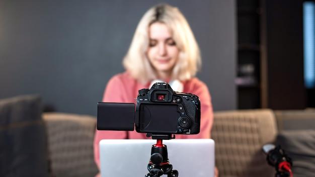 Het jonge blonde meisje van de maker van de inhoud ligt op haar laptop op de tafel. zelf filmen met een camera op een statief. werken vanuit huis. vlog opnemen