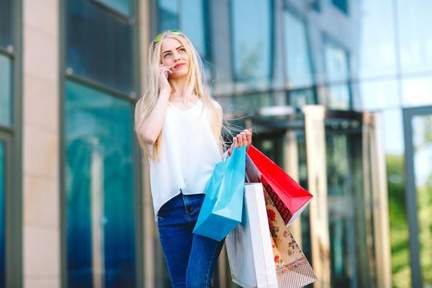 Het jonge blonde meisje van het levensstijlportret, met het winkelen zakken die van winkel opstappen en door mobiele telefoon spreken.