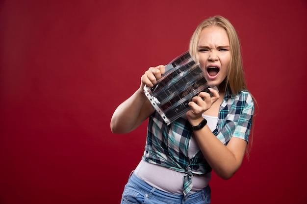 Het jonge blonde model controleert de scènes van de polaroidfilm en kijkt ontevreden en doodsbang.