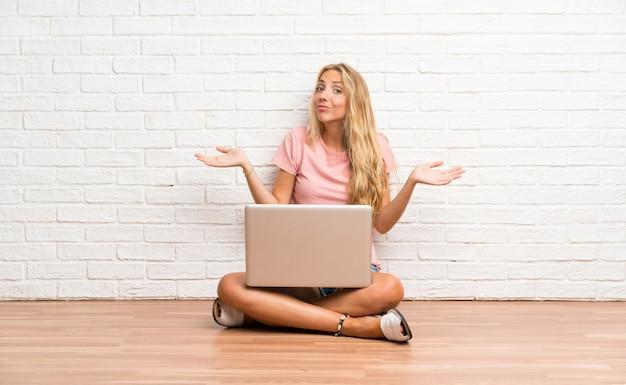 Het jonge blonde studentenmeisje met laptop op de vloer die twijfels hebben met verwart gezichtsuitdrukking