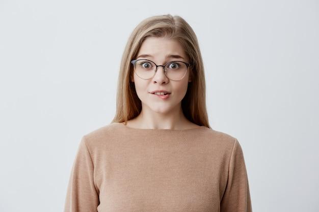 Het jonge blonde wijfje dat ongerust gemaakt heeft kijkt bijt zenuwachtig kijkend haar onderlip kijkend met bezorgde ogen door modieuze eyewear. vrouw in losse bruine trui met nerveuze uitdrukking