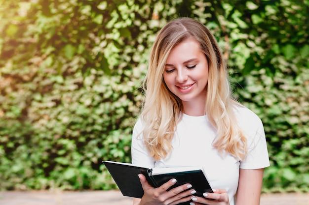 Het jonge blondemeisje zit op een bank, leest een boek en glimlacht in een park op een achtergrond van bomen en struiken