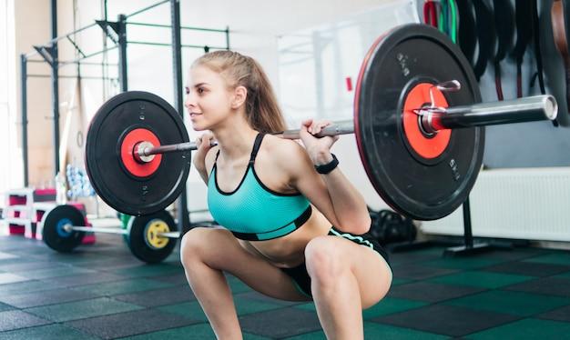 Het jonge blondevrouw doen die met een barbell op de schouders in de gymnastiek hurken