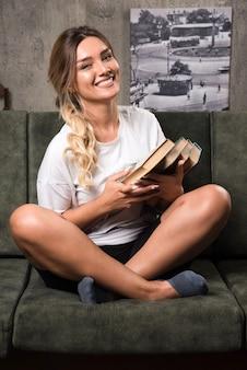 Het jonge boek van de vrouwenholding met gelukkige uitdrukking zittend op de bank.