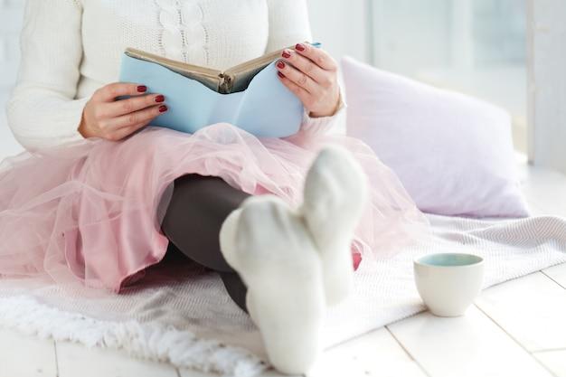 Het jonge boek van de vrouwenlezing en het zonnebaden met plaid en koffie